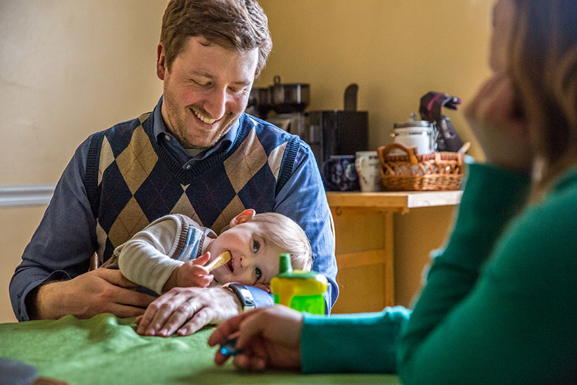 Steven and Liz Callen sat at their kitchen table with their son, Simon, in 2018. The Callens received a grant from the Archbishop Robert J. Carlson Adoption Fund to help in their adoption.