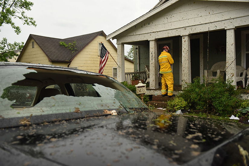 A firefighter checks houses May 23 following a tornado in Jefferson City, Mo. The May 22 tornado tore apart buildings in Missouri's capital city as part of an overnight outbreak of severe weather across the state that left at least three people dead and dozens injured.