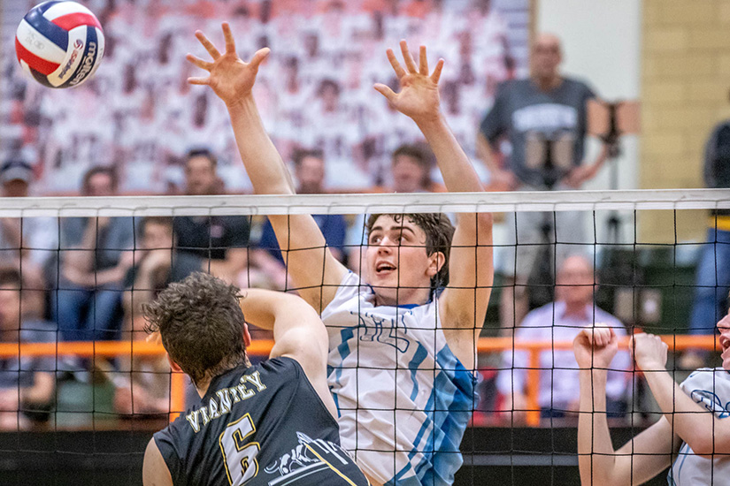 St. John Vianney High School's Alex Whitesides hit the ball as St. Louis University High School's Andrew Cross guarded the net. SLUH beat Vianney to win the Class 4 volleyball state championship.