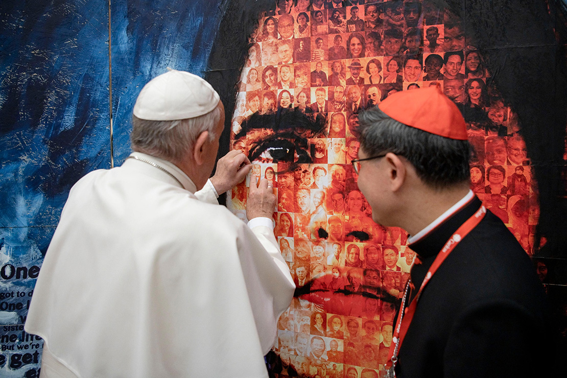"Pope Francis placed a picture of his parents onto the ""Share the Journey"" photo mosaic during an audience with delegates attending the general assembly of Caritas Internationalis at the Vatican May 27. At right is Philippine Cardinal Luis Antonio Tagle of Manila, president of Caritas Internationalis. The mosaic of migrants, world leaders and Caritas workers illustrates how humanity forms one family and is sharing one journey. Being part of one family, Cardinal Tagle said, also means sharing responsibility for the family home, which is the earth. Efforts to protect human beings and protect the environment at the same time are part of what the Catholic Church calls ""integral ecology."""