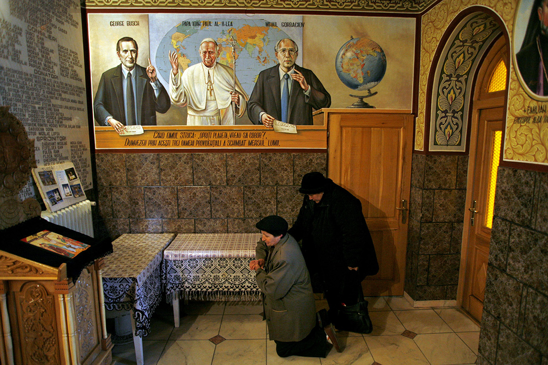 People prayed at an Orthodox church with portraits of former U.S. President George Bush, Pope John Paul II and ex-soviet leader Mikhail Gorbachev painted on the walls in the village of Petresti, 205 miles northwest of Bucharest, Romania, in 2008. Pope Francis is scheduled to visit Romania May 31-June 2.