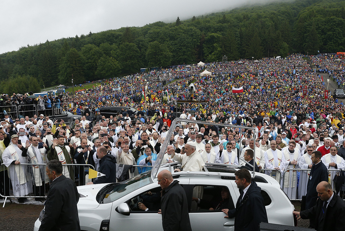 Pope Francis greeted the crowd before Mass at the Marian shrine of Sumuleu Ciuc in Miercurea Ciuc, Romania, June 1. Tens of thousands of people attended the Mass despite rainy weather.