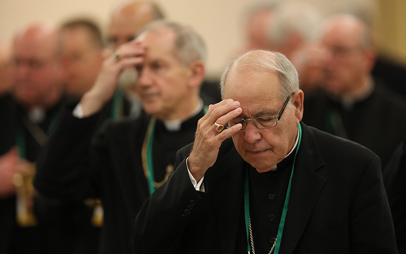 Bishop Felipe de Jesus Estevez of St. Augustine, Fla., and other prelates crossed themselves at the conclusion of morning prayer during the spring general assembly of the U.S. Conference of Catholic Bishops in Baltimore June 13.