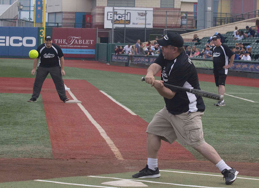 Father James Kuroly swung at a pitch while Father Chris Bethge led off first base during Collars vs. Scholars games at MCU Park on Coney Island in Brooklyn June 17. For the second straight year, the Brooklyn clergy showed their prowess on the softball diamond with a 2-1 win over principals and teachers of diocesan schools.