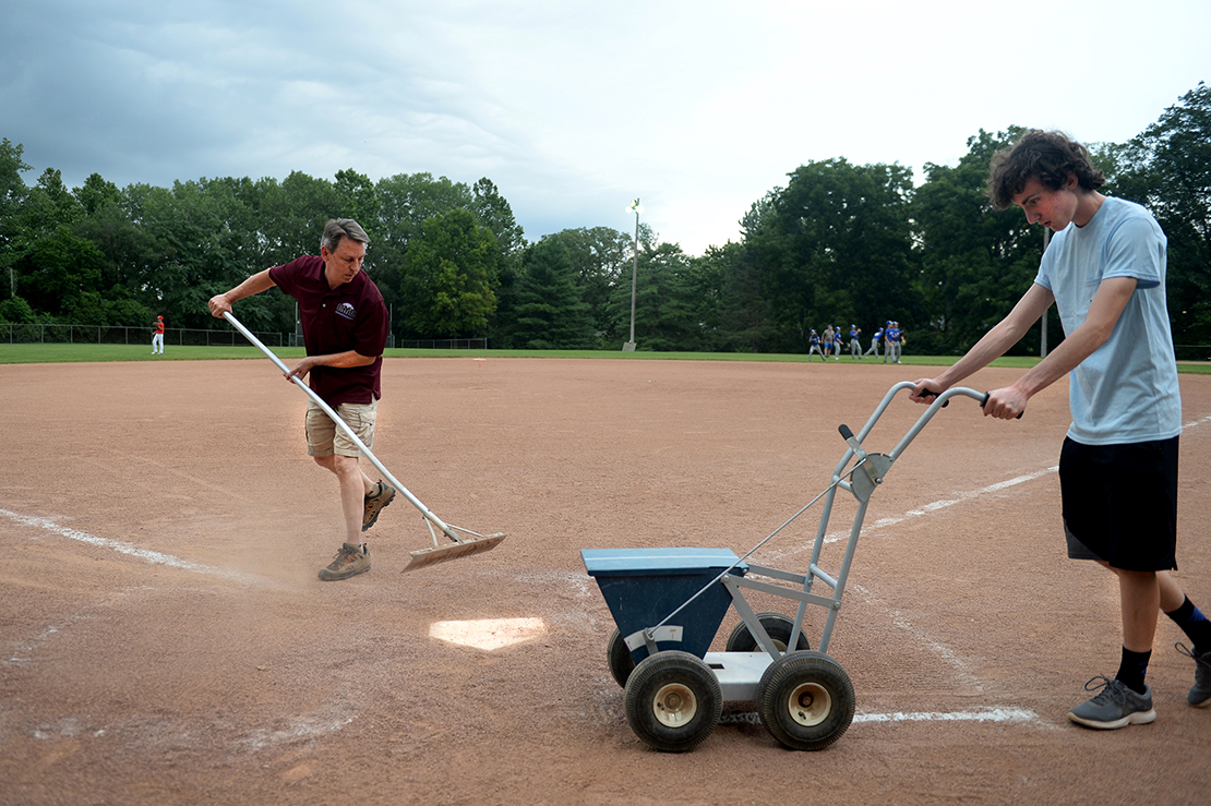 "Tom Grassi, left, and his son, Brian, prepared the baseball diamond at the Kermit C. Albus Memorial Field at St. Elizabeth of Hungary Church in Crestwood. The Grassis are members of Mary Queen of Peace Parish's ""field maintenance ministry,"" which maintains and uses the field for its Catholic Youth Council teams."