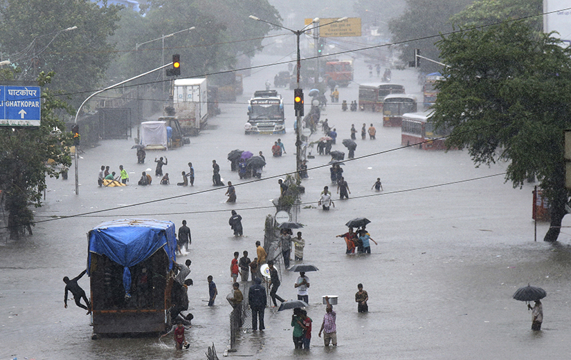 People walked through a flooded street following heavy monsoon rains in Mumbai, India, Aug.4. 2019. Cardinal Oswald Gracias of Mumbai, India, and Syro-Malabar Bishop Thomas Elavanal of Kalyan, India, have asked parish priests Aug. 5 to help stranded and homeless people as heavy rain continued in western India.