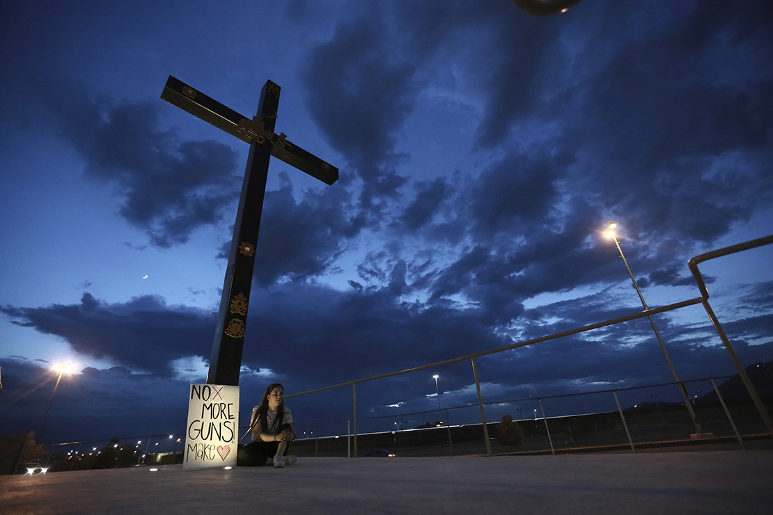 A woman was among those who held a vigil in Juarez, Mexico, Aug. 3, for the 3 Mexican nationals who were killed in an El Paso shopping complex.