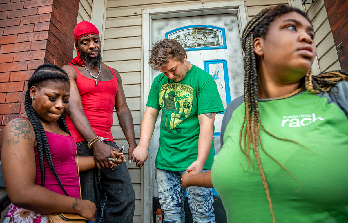 Patricia Henderson, Ifiok Usanga, Daniel Andrews and Dana Holden held hands during a prayer vigil Aug. 14 held for Usanga's 7-year-old son, Xavier Usanga, who was shot and killed outside his home Aug. 12.