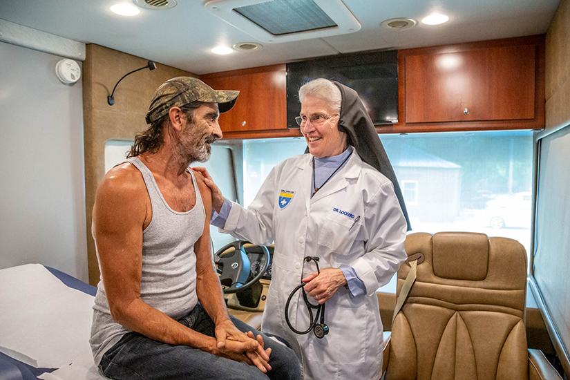 Physician Sister Marie Paul Lockerd, RSM, talked to Chip Hawkins during a check-up at the Rural Parish Clinic located at St. Joachim Parish Center in Old Mines. The clinic is up and running, providing health care services to the uninsured poor in Washington County.