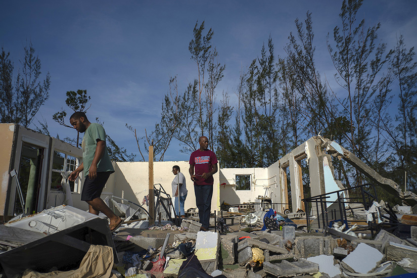 George Bolter, left, and his parents walk through the remains of his home destroyed by Hurricane Dorian in the Pine Bay neighborhood of Freeport, Bahamas, on Sept. 4. Rescuers trying to reach drenched and stunned victims in the Bahamas fanned out across a blasted landscape of smashed and flooded homes Sept. 4, while disaster relief organizations rushed to bring in food and medicine.