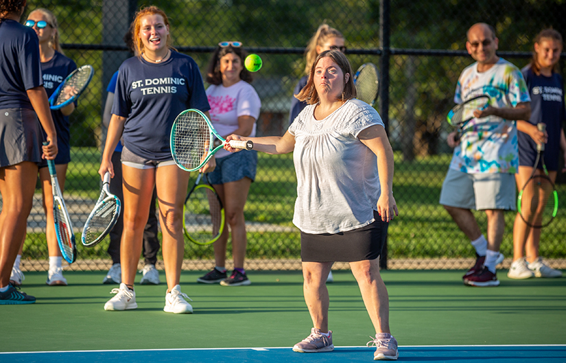 Megan Layton returned the ball across the net as the St. Dominic High School tennis team taught the game of tennis Sept. 4 to residents of St. Louis Life, a community-based, residential program for adults with developmental disabilities.