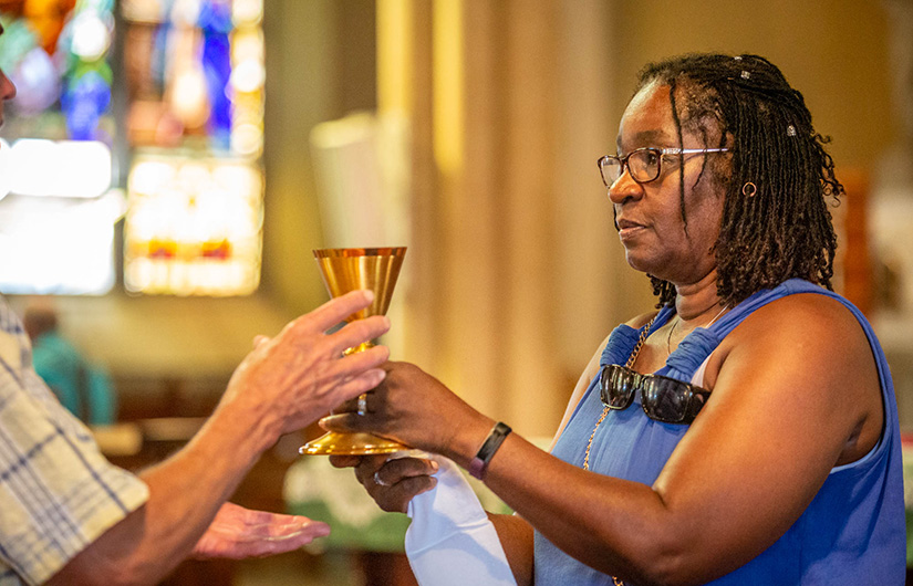Brenda Tillman distributed the Precious Blood during Mass at Most Holy Trinity Church on Sept. 15.