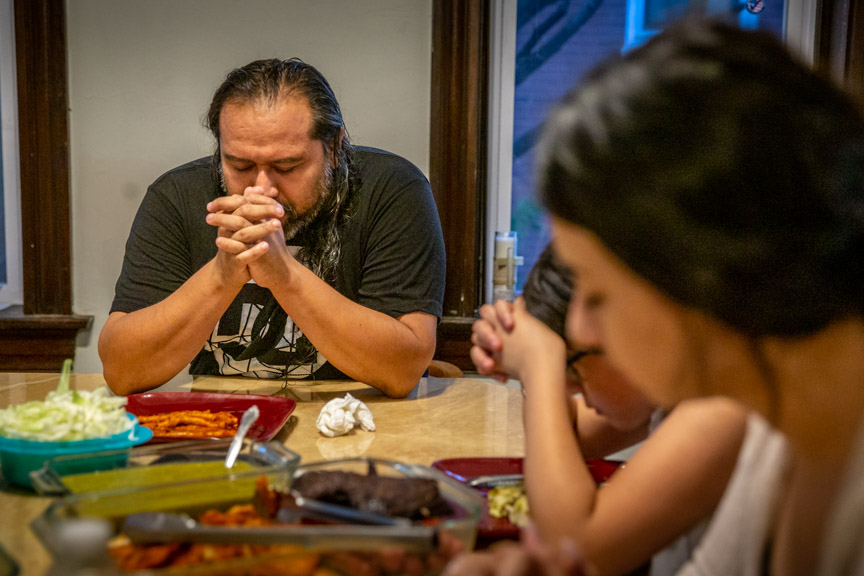 Daniel Mendoza led his family in prayer before they ate enchiladas at dinner celebrating 18-year-old Ashley's birthday at the Estrada-Mendoza home in St. Louis, MO on Thursday, Sep. 12, 2019.
