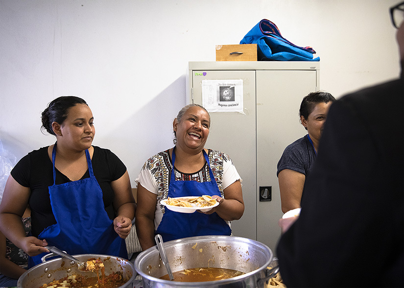 Migrants shared a light moment while serving food to a delegation of U.S. bishops and Church leaders Sept. 24 at Corpus Christi Church in Ciudad Juarez, Mexico. The Sept. 23-27 pastoral visit, sponsored by various offices of the U.S. Conference of Catholic Bishops and other national organizations, aimed to highlight the Church's ministry to migrants, the border conditions and immigration laws affecting them, and their material and spiritual needs.