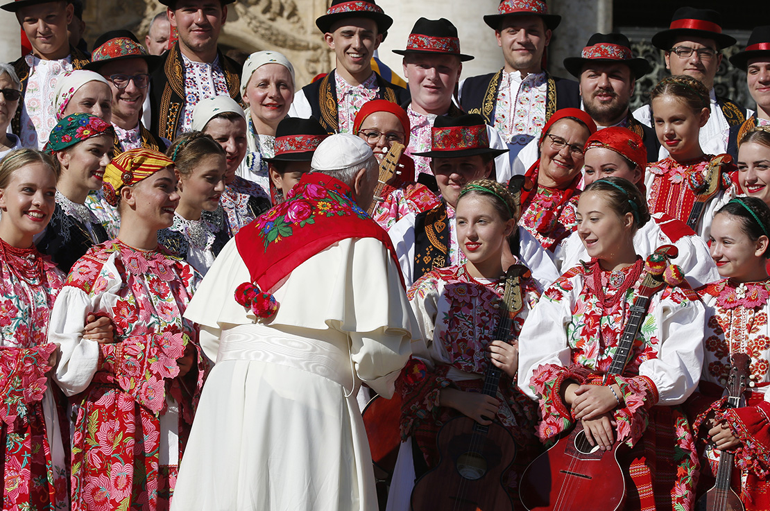 Pope Francis spoke with members of a dance group from Croatia during his general audience in St. Peter's Square at the Vatican Oct. 9.