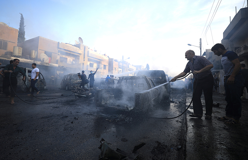 A man sprayed water at the site of a car bomb blast in Qamishli, Syria, Oct. 11. The ongoing Turkish military operation in northeastern Syria is having a devastating humanitarian impact on civilians, according to humanitarian groups.