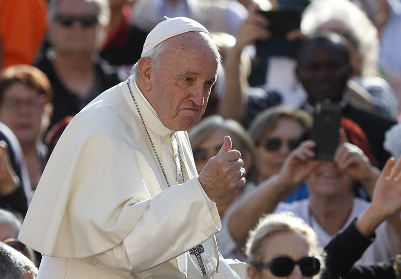 Pope Francis gave a thumbs-up as he greeted the crowd during his general audience in St. Peter's Square at the Vatican Oct. 16.