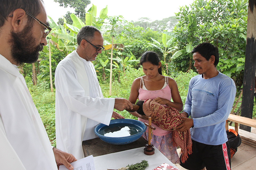 Father Miguel Angel Cadenas, a Spanish Augustinian missionary, baptized an infant in an Urarina indigenous community on Peru's Urituyacu River.