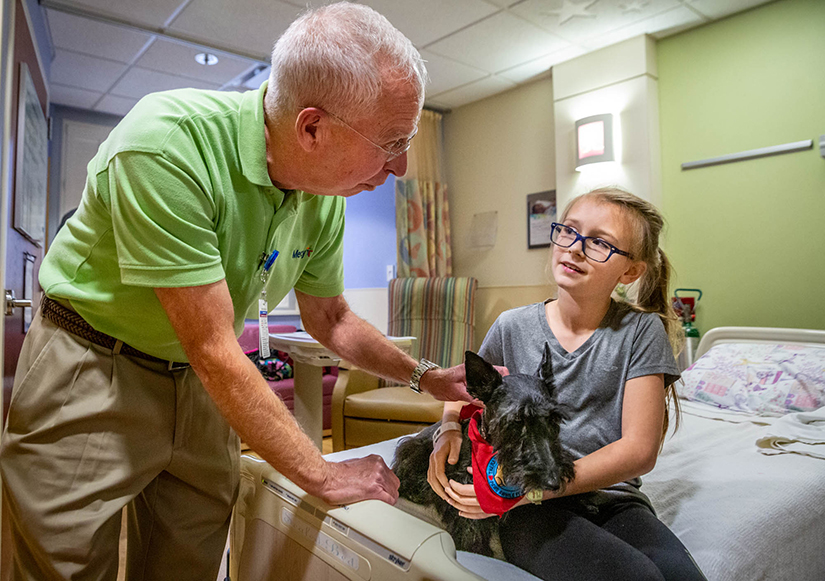 Ten-year-old Audrey Hoffmann met Deacon Lonnie Weishaar and his therapy dog, Sadie, a Scottish Terrier, at Mercy Hospital St. Louis in Creve Coeur on Oct. 29. Deacon Weishaar estimates he has visited more than 400 patients with Sadie.