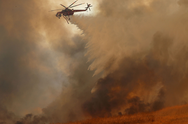 A helicopter dropped water on a fast moving wildfire Oct. 9, 2017 in Orange, Calif. Climate scientists attribute increased fire occurrences in part to warm, dry weather patterns caused by global climate change.