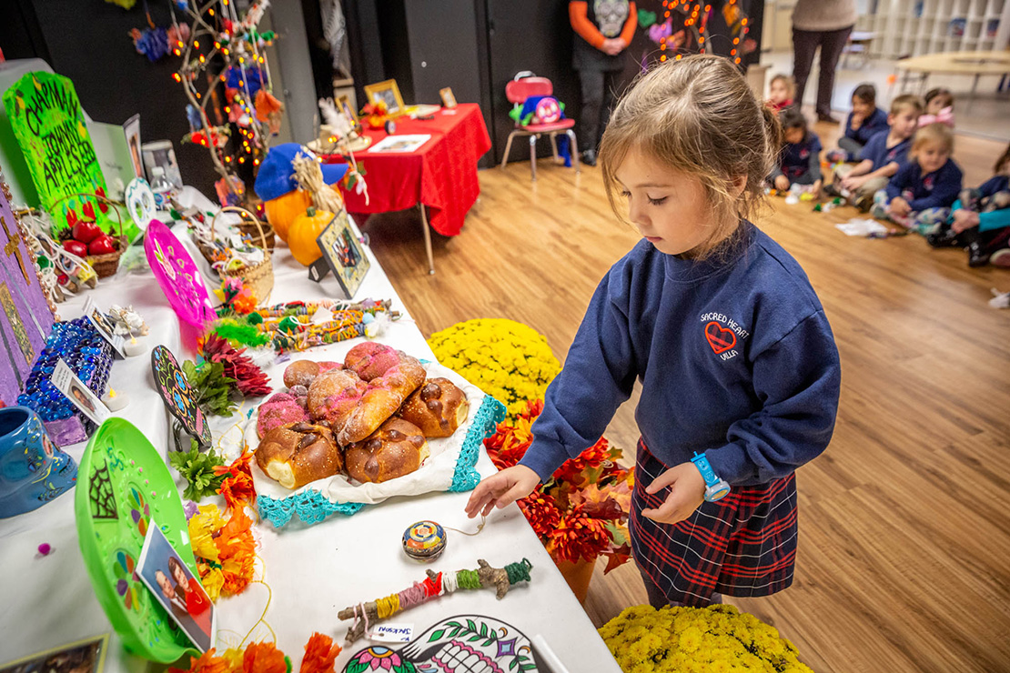 Kindergartener Quinn Franceschi placed her great-grandfather's yo-yo on the Dia de los Muertos altar at Sacred Heart Villa School in St. Louis on Oct. 30.
