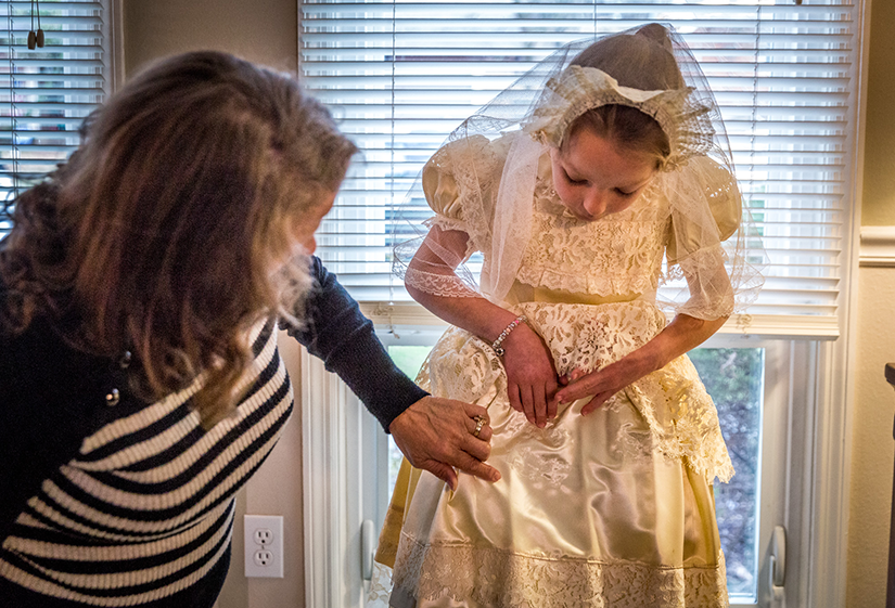 Paula Hrin adjusted the First Communion dress on her granddaughter, Vanessa Hrin, pointing out where her name was embroidered. In 1959, Paula's mother, Dolores Perniciaro, made a First Communion dress for Paula; this April, Vanessa will be the 16th family member to wear the dress for her First Communion.