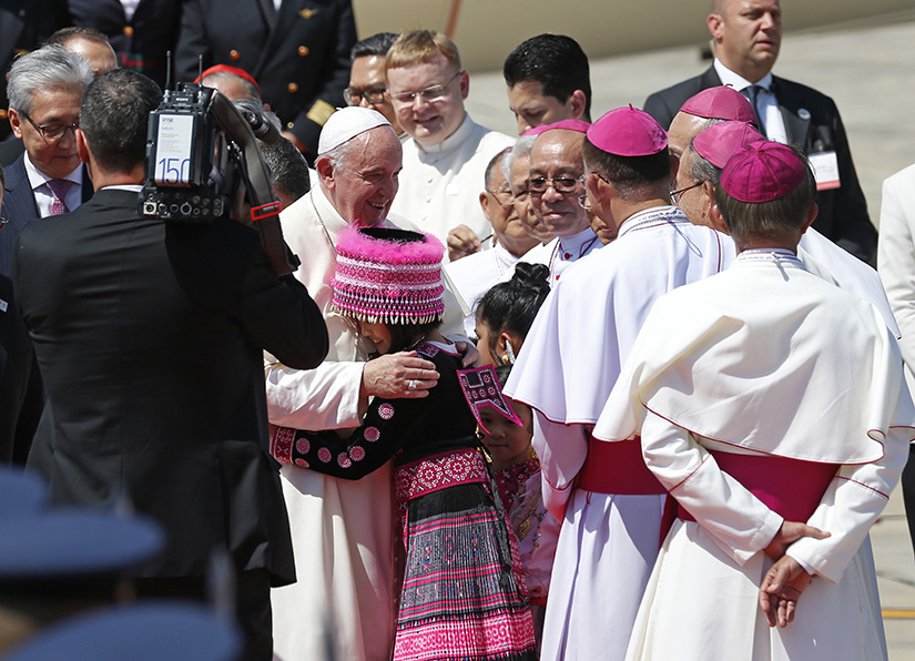 Pope Francis embraced a girl in traditional dress as he arrived at Military Air Terminal 2 in Bangkok Nov. 20, 2019. The pope is visiting Thailand and Japan Nov. 20-26.