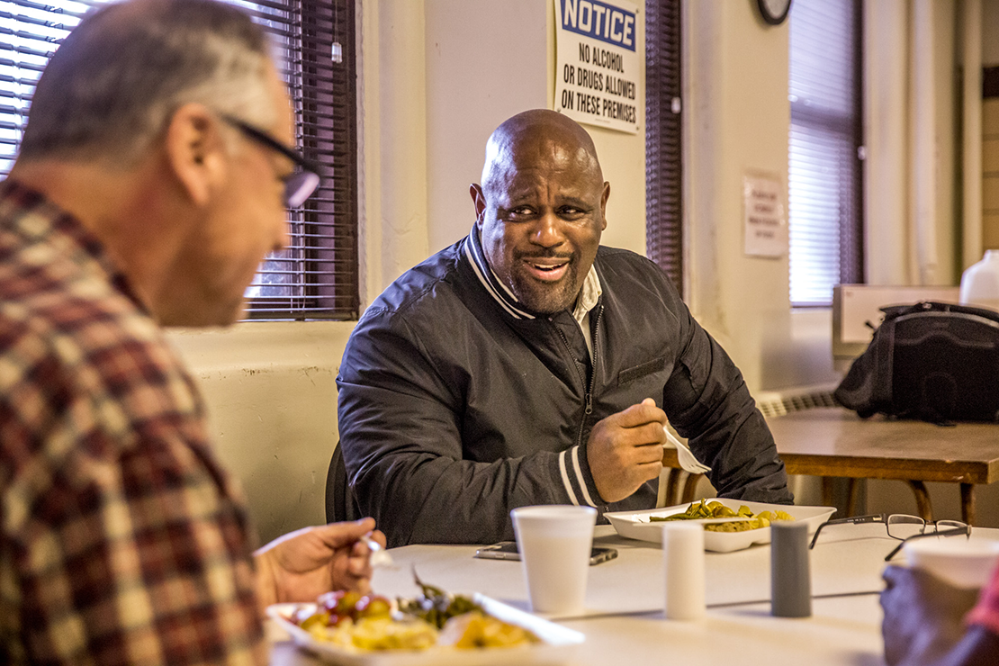 "Father Dempsey's Charities director Sam Irons ate dinner with resident Charles Phillips. ""I try to treat people with compassion,"" he said, a trait he learned by watching Archbishop Robert J. Carlson during their time together."