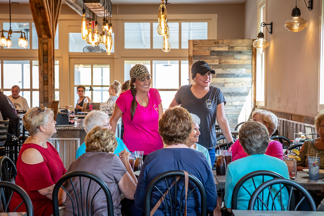 Sisters Cami Flynn, left, and Cori Breen talk to customers who are eating lunch at The Grotto in Flint Hill. Flynn and Breen operate The Grotto Grill and make sure that the restaurant reflects their faith lives.
