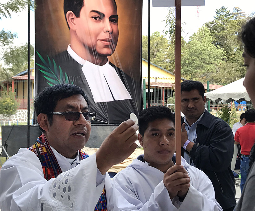 A clergyman distributed Communion during the beatification Mass of Blessed James Miller in Huehuetenango, Guatemala. Blessed Miller, a De La Salle Christian Brother, went through formation at La Salle Institute in Glencoe.