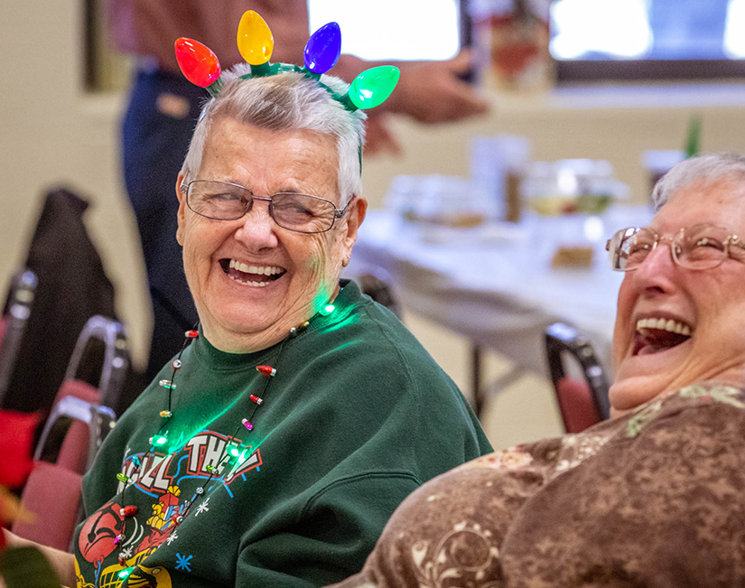 Pat Walkenhorst, left, laughed with her friend Connie Zurawski as they ate lunch with more than 200 seniors at St. Robert Bellarmine Parish in St. Charles Dec. 4. The parish hosts the senior luncheon every month except for January and July.