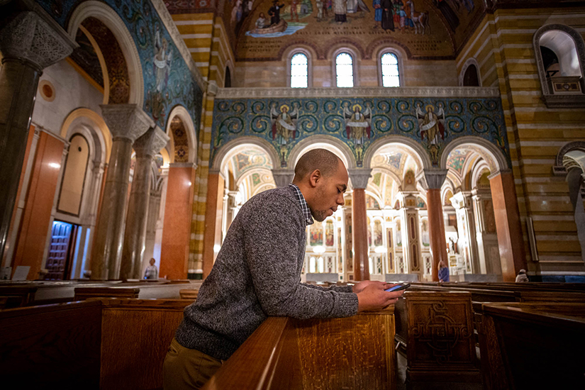 Louis Jones, an intern with the Catholic Campaign for Human Development, prayed before Mass at Cathedral Basilica of Saint Louis Dec. 10. Jones was drawn back to his Catholic faith after reading more about Catholic social teaching.