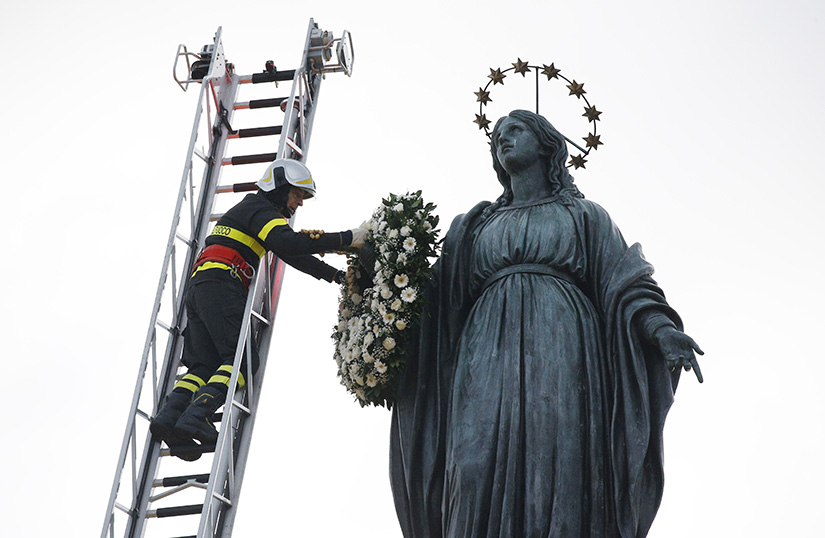 A firefighter placed a wreath on a Marian statue overlooking the Spanish Steps in Rome Dec. 8, the feast of the Immaculate Conception. Later in the day, the pope recited a prayer he wrote for the occasion.