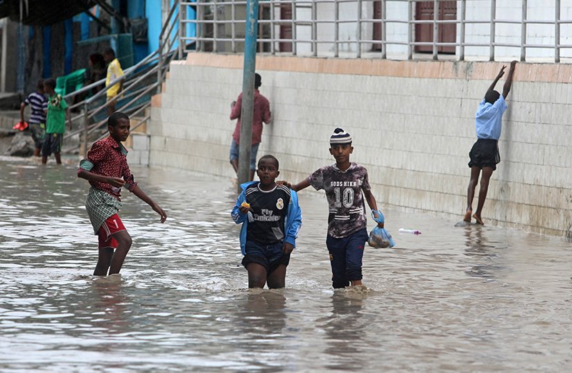 Young Somalis walked through floodwaters after heavy rains in Mogadishu Nov. 26. Caritas, the relief arm of the Catholic Church, has delivered food aid to Muslims in Somalia, who are currently facing floods and living in a fragile peace environment due a prolonged Islamist insurgency.