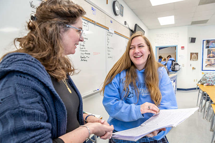 "Hanna Vanourney excitedly showed teacher Denise Bossert how many notes she took during apologetics class at St. Dominic High School Jan. 13. ""I'm in campus ministry,"" she said, ""and I never heard any of this stuff before today!"""