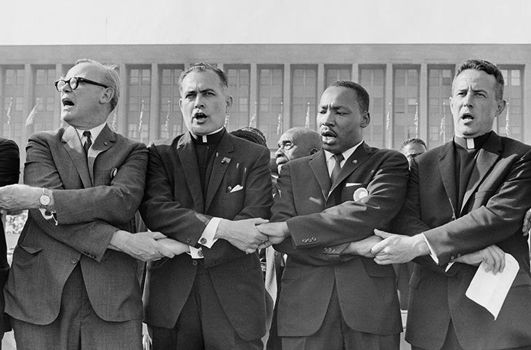 Holy Cross Father Theodore Hesburgh, then president of the University of Notre Dame, second from left, joined hands with the Rev. Martin Luther King Jr., the Rev. Edgar Chandler and Msgr. Robert J. Hagarty of Chicago, far right, in this 1964 file photo. Fifty years after Rev. King's assassination, advocates say there is still work to do in dismantling racism.