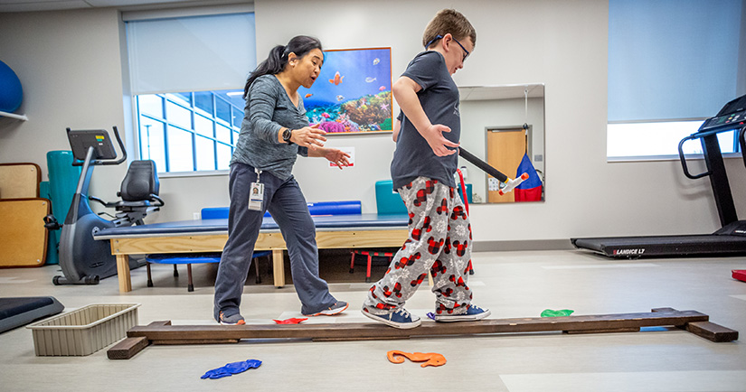 Eight-year-old Isaac Vincent walked on a balance beam with physical therapist Bing Sabino at SSM Health Cardinal Glennon Pediatrics Specialty Services in south St. Louis County. The facility is one way that Cardinal Glennon is reaching out beyond its hospital setting.