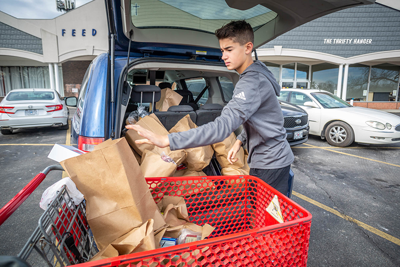 Andrew Ecker, a freshman at Chaminade College Preparatory High School, loaded a van filled with food for a family of six at Feed My People in Lemay Feb. 3. Ecker serves at the food pantry with his grandfather, Deacon Richard Schellhase of Queen of All Saints Parish.