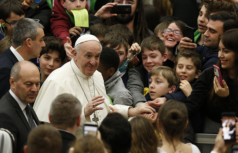 Pope Francis greeted the crowd as he arrived for his general audience in Paul VI Hall at the Vatican Feb. 5.