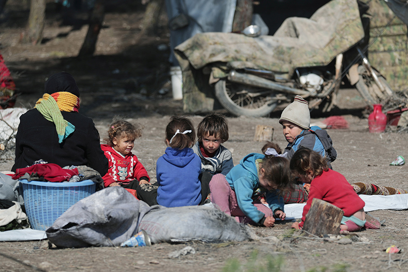 Syrian children sat on the ground at a makeshift camp in Qatmah Feb. 17. Syrian government forces and Russian warplanes are bombing Idlib province, while tens of thousands of people are sheltering under strips of plastic tenting in the freezing cold and snow.
