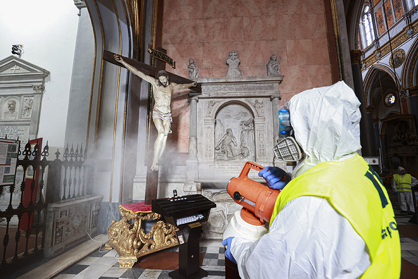 A worker sprayed disinfectant to combat the coronavirus in the Basilica of San Domenico Maggiore in Naples, Italy, March 6. The suspension of public Masses in Italy is a painful yet necessary measure to protect people's health, the country's bishops said in a March 8 statement.