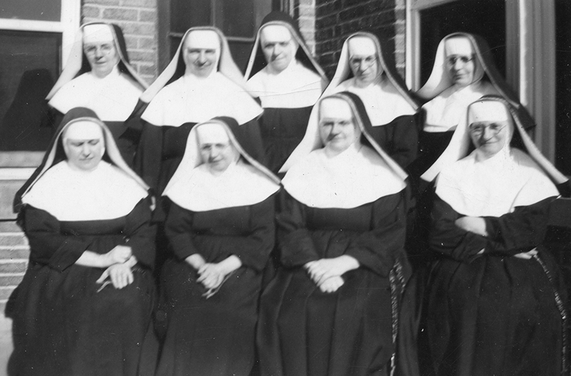 The Sisters of Charity of Zams gathered outside Kenrick Seminary. Shown, from left, are Sisters Dominata, Goberta, Frances, Bernarda, Villanova and, in the bottom row, Sisters Killiana, Helen, Theophilia and Adelharda. During the years leading up to the U.S. entrance into World War II and tightening immigration limits, the women religious from the community based in Austria ran into roadblocks when trying to work in their ministries in the United States, including at Kenrick Seminary in Shrewsbury.