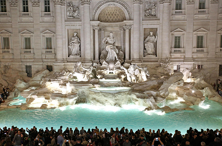 People gathered in front of the landmark Trevi Fountain after its 2015 restoration in Rome. While millions of tourists throw a coin over their shoulder into the fountain hoping to return to Rome one day, the money scooped out of the fountain each week offers more concrete hope to the city's poor.