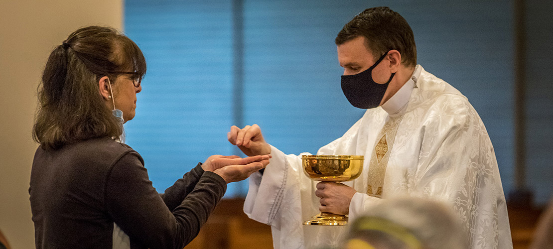 Father Anthony Yates distributed the Eucharist to during one of the first celebrated public Mass since the COVID-19 shut down at St. Francis of Assisi Parish church on Monday, May 18.