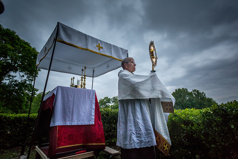 "Father Aidan McDermott, OSB, offered Benediction during Eucharistic adoration at St. Louis Abbey. ""It's bringing Christ to the streets,"" Father McDermott said, noting that he views it as a part of the new evangelization in reaching out to people."