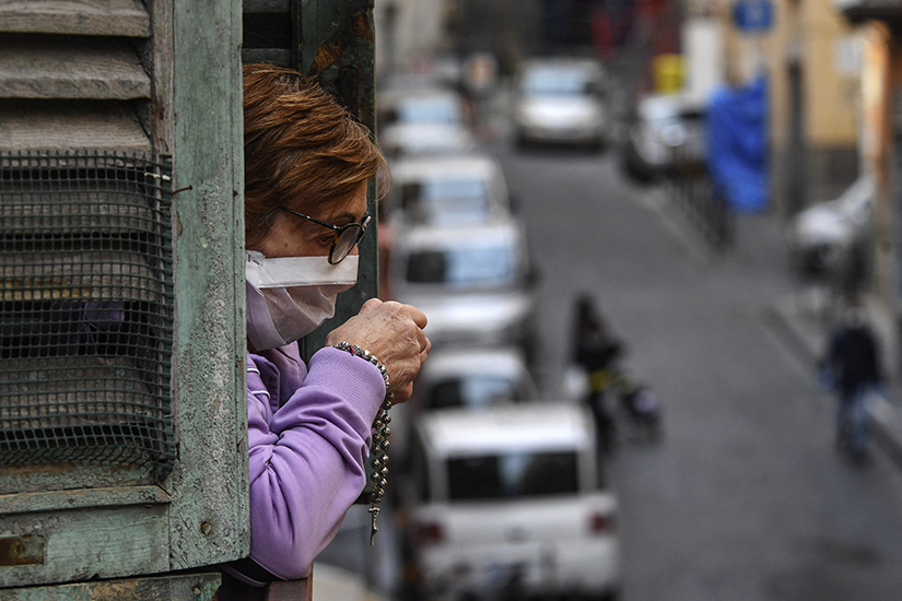 A woman prayed in a window opening overlooking a street in Milan, Italy, March 21 during a nationwide lockdown to reduce the spread of COVID-19. A recent study showed an increase in prayer and religious fervor in Italy amid the coronavirus pandemic.