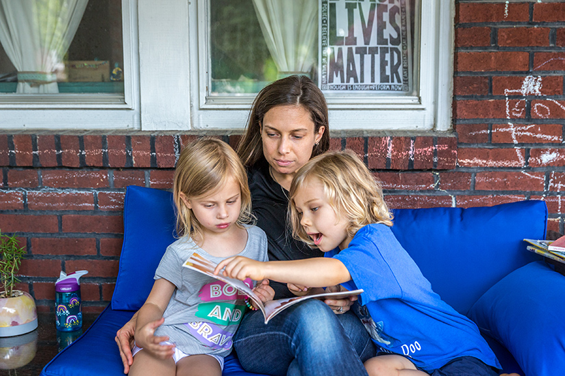 "Teresa Steinkamp read ""The Color of Us"" by Karen Katz to her children Madeline and Keller on their porch on June 12. Steinkamp, a parishioner at St. Cronan Parish in St. Louis, is a volunteer faciliator with We Stories' Family Learning Program."