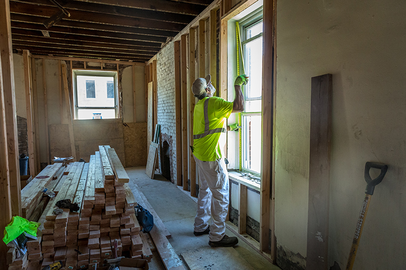 Tony Miller measured the inside of a window frame as St. Joseph Housing Initiative renovates a home in St. Louis on June 11. The initiative rehabs homes to produce quality housing for low- and moderate-income families in the St. Louis area.