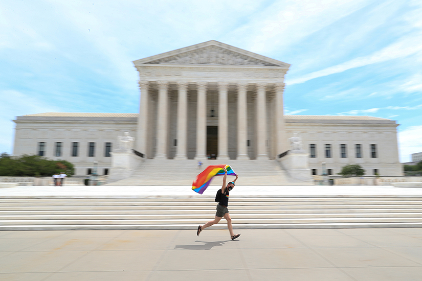 A person celebrated in front of the U.S. Supreme Court building in Washington June 15. In a 6-3 vote that same day, the Supreme Court said LGBT people are protected from job discrimination by Title VII of the Civil Rights Act of 1964.