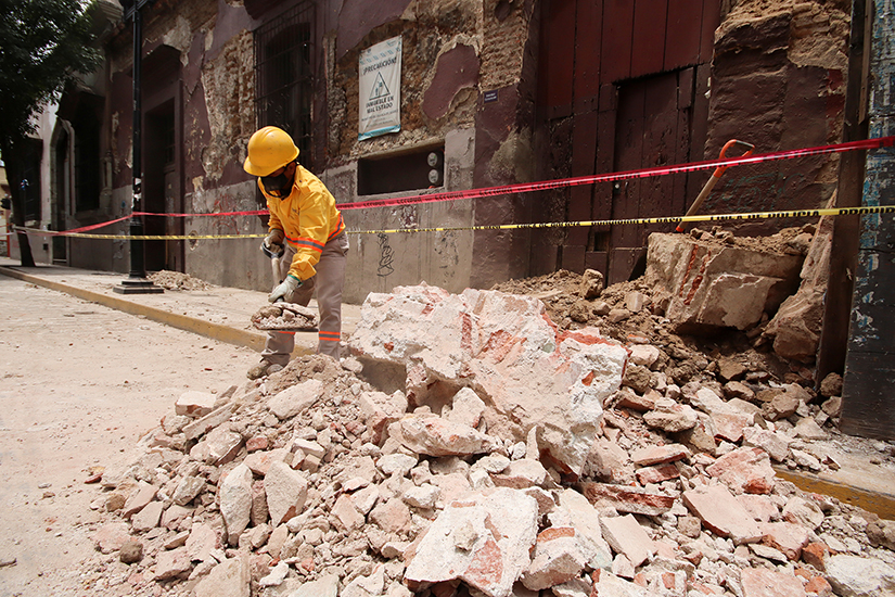 A worker cleared debris from a building in Oaxaca, Mexico, June 23, following an earthquake. The quake struck as COVID-19 cases are increasing and people are wary of going to the hospital.